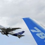 The vertical stabilizer of a Boeing 787 Dreamliner is seen as an Airbus A380 takes off during the 49th Paris Air Show at the Le Bourget airport near Paris